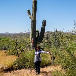 Karen Overton, The Quilt Rambler, poses by a tall cactus in Arizona