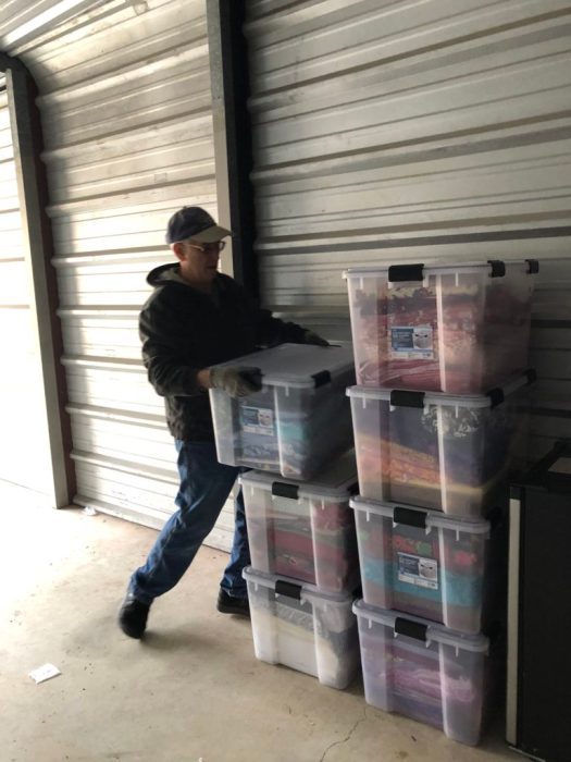 man moving boxes into a storage unit