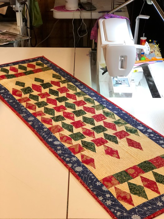 Silver and Gold thread was used to quilt this Christmas version of Refraction pattern by Studio 180 Design