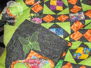 Hand guided butterfly logo of Karen Overton as a signature on My Dangling Carrot quilt
