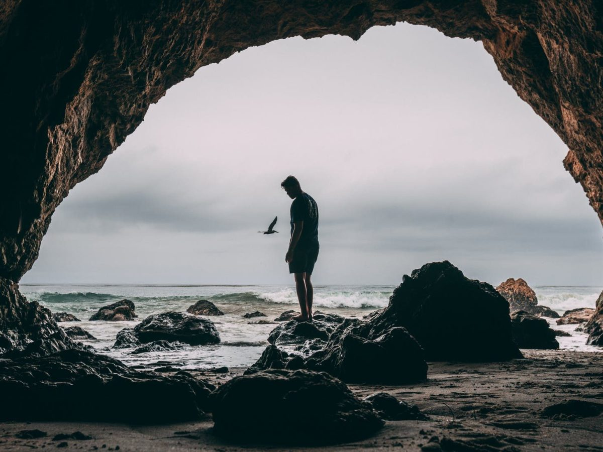 photo of man standing on rock near seashore