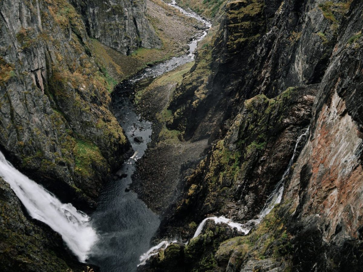 fast waterfalls flowing into river between mountains