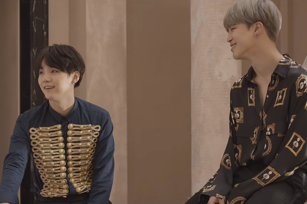 Yoongi and Jimin sit together after goofing off in the museum-like room.