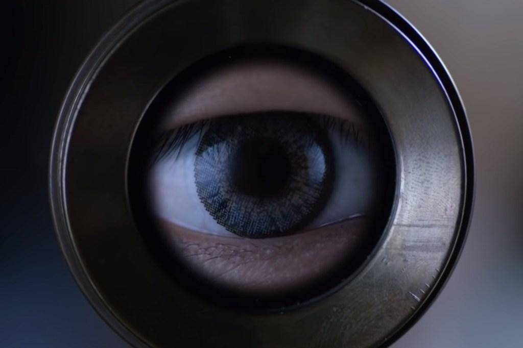 An eye is seen gazing through the lens of a telescope