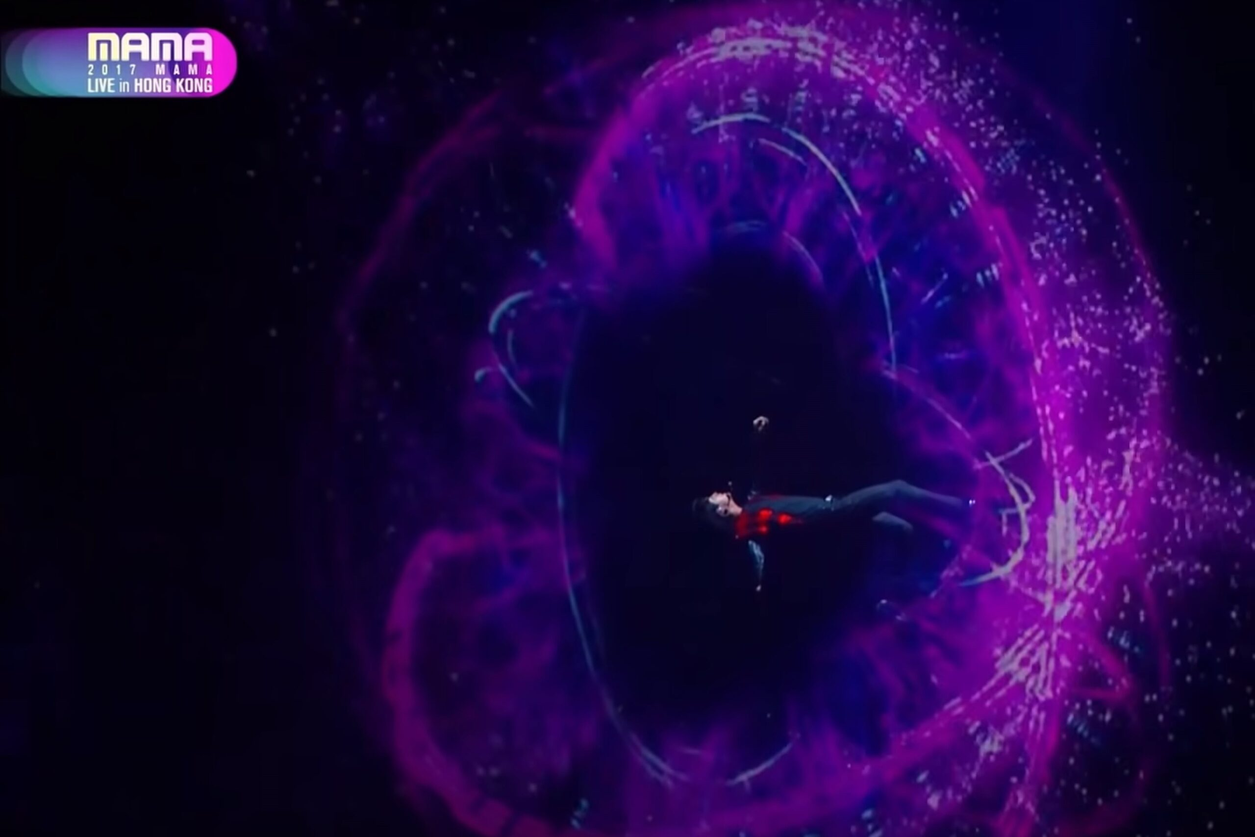 Jin is suspended in a fall at the center of a wormhole during the 'Beyond Wormhole' performance at MAMA 2-18