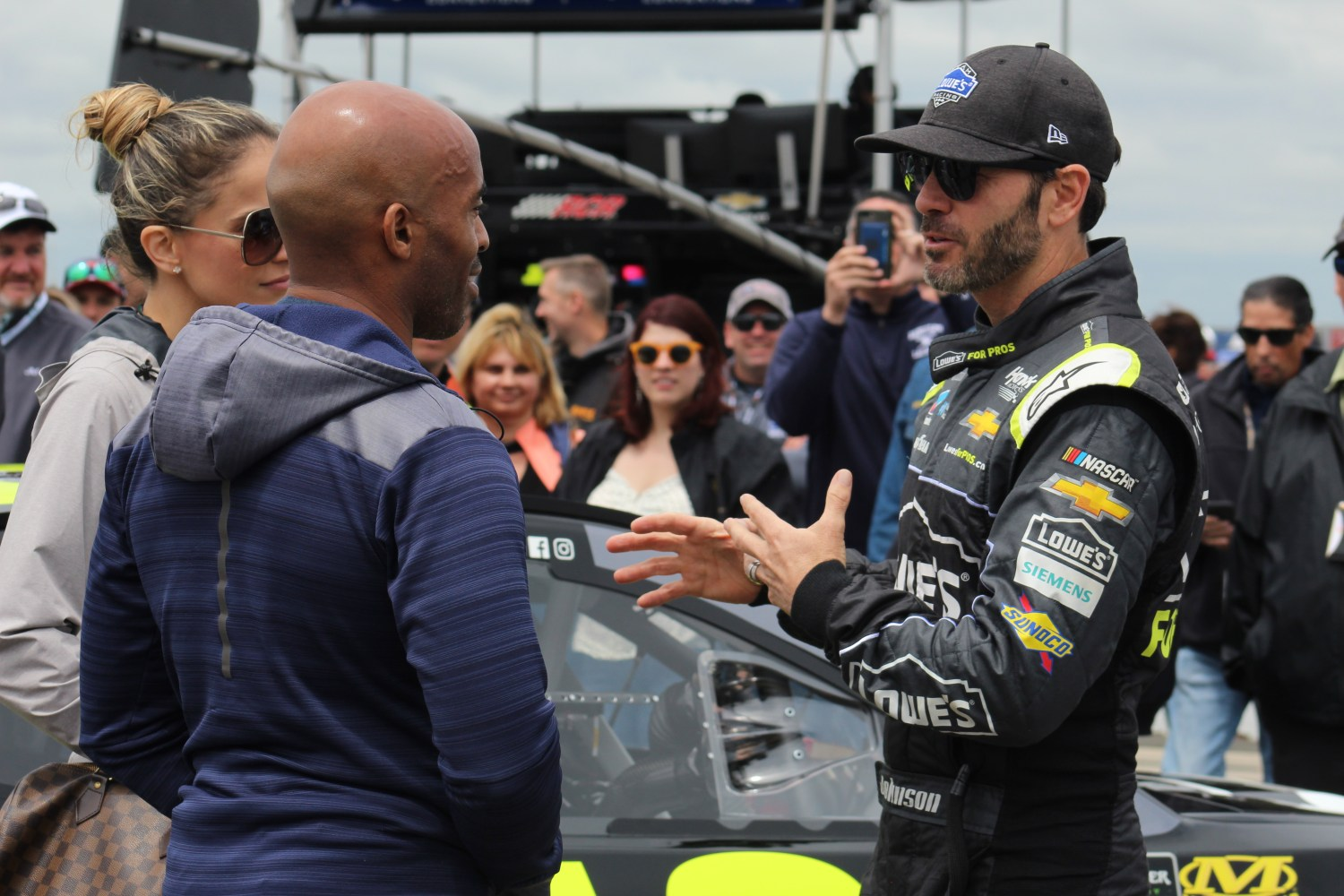 Jimmie Johnson (right) chats with Tiki Barber (left) on pit road ahead of the 2018 Pocono 400. (Tyler Head | The Racing Experts)