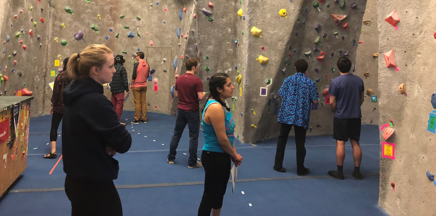 Climbers plan their routes at UWL's Back to the 80's Bouldering Competition