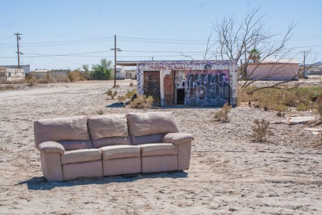 An abandoned couch rests in front of a dilapidated graffiti shack at Salton Sea Beach.