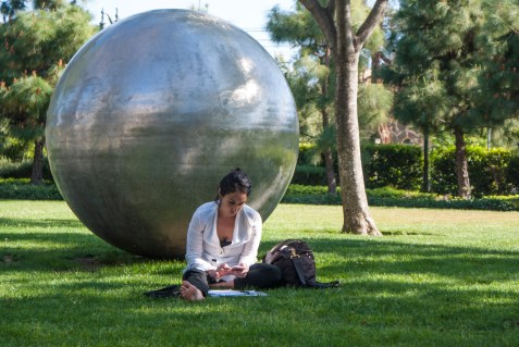 A student sits in the grass, cell phone in hand, in front of an artwork-filled lawn at USC.