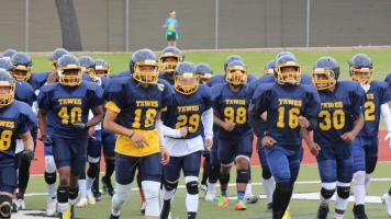 Some players on the blue team running back to the sidelines after doing a drill at halftime. Photo by Matt Smith.