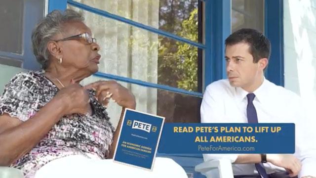 Mayor Pete Buttigieg listens to an African-American woman speak.
