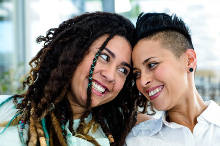 Close-up of lesbian couple looking at each other, smiling. Signifies reduced conflict and improved emotional connection after attending a couples therapy retreat for lesbians or a lesbian friendly couples workshop.