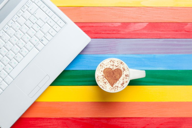 Table with colors of lgbt community and keyboard and cappuccino. This signifies online relationship coaching for lesbian couples and lgbt couples.