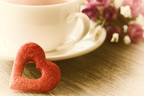 Cup of coffee with heart cookie and flowers nearby. Signifying improved relationship and a better connection after attending an ONLINE hold me tight relationship enhancement program for couples.