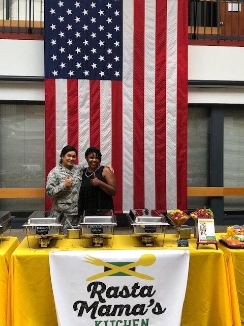 Chantoll Williams and a happy customer give thumbs ups in front of an American Flag behind a table of catered food.