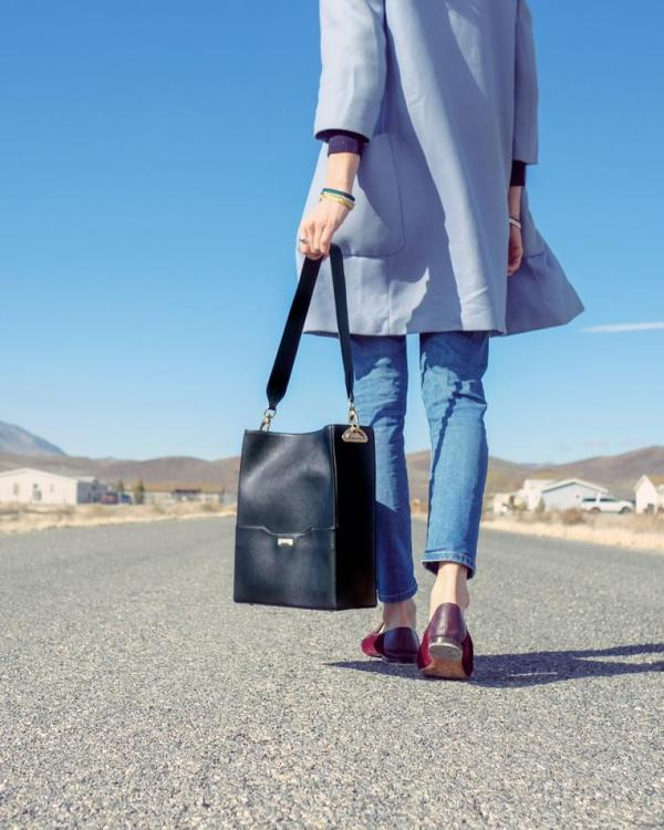 Model walking in the desert with a black vegan bucket bag