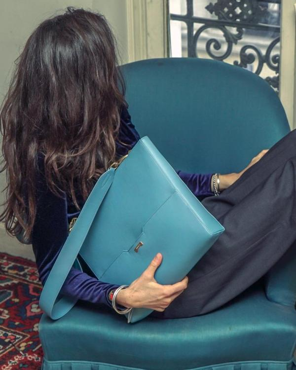 Luxury Parisian flat with a model holding a the perfect light blue vegan leather laptop bag