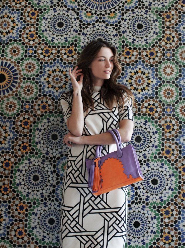 Model holding Asmaa Purple Leather Mini Bag against a moroccan wall