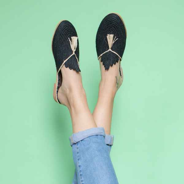 feet model in front of a light green background wearing jeans and abury black raffia summer slippers with tassel
