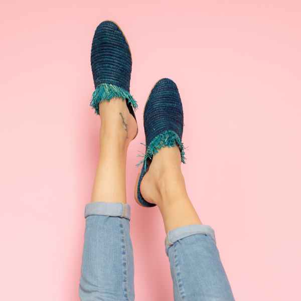 feet model in front of a pink background wearing jeans and abury blue raffia summer slippers with fringes