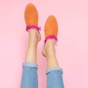feet model in front of a pink background wearing jeans and abury orange raffia summer slippers with fringes