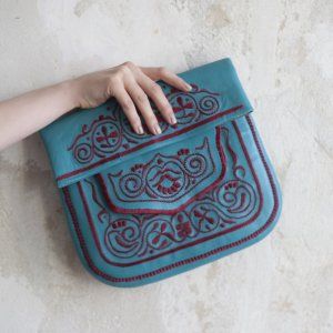 hand holding blue and red handmade embroidered ABURY Leather Berber Shoulder Bag before wall