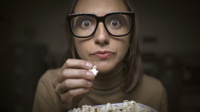 woman with glasses eating popcorn