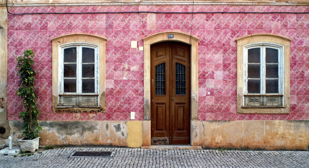 A rustic pink building in an old town in the Algarve, which are great for exploring when on an Algarve weekend break