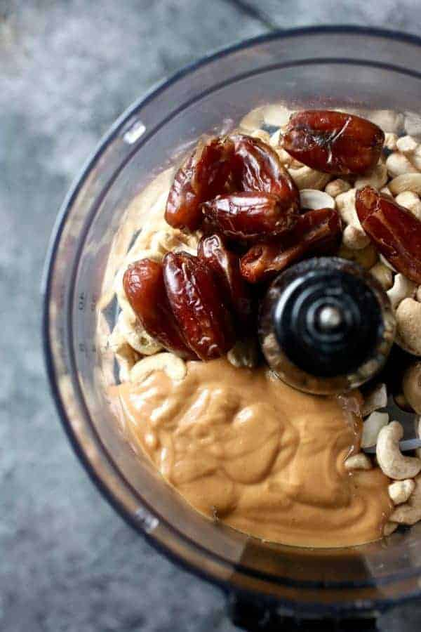 Overhead shot of food processor filled with dates, nut butter and cashews, the ingredients for the Nutty Butter Bites.