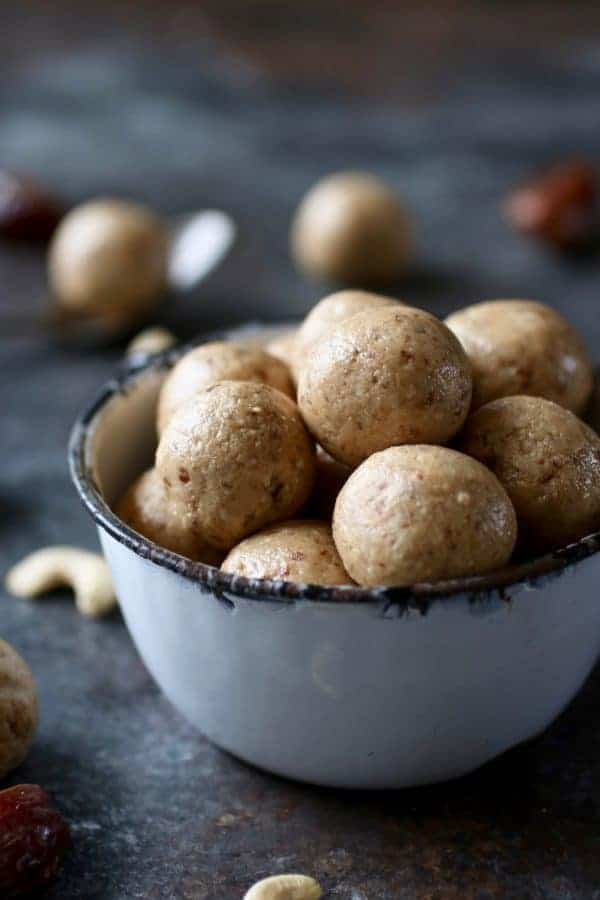 Straight on photo of Nutty Butter Bites in a tea cup with cashews and dates surrounding.