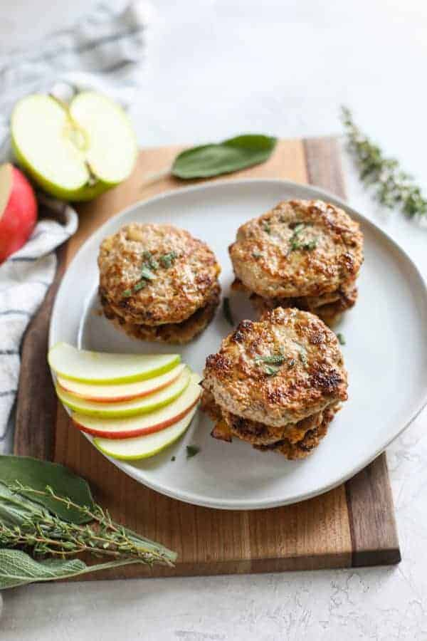 Turkey Apple Sausage Patties stacked by twos on a white plate with apple slices on the side