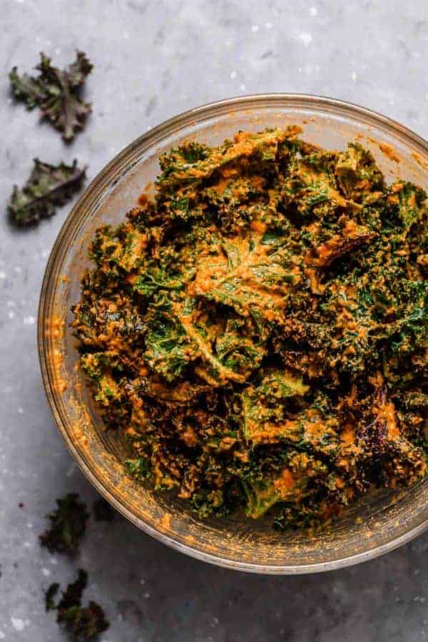 Overhead photo of the Cheese Pizza Kale Chips in a bowl tossed in the orange sauce and ready for the oven.