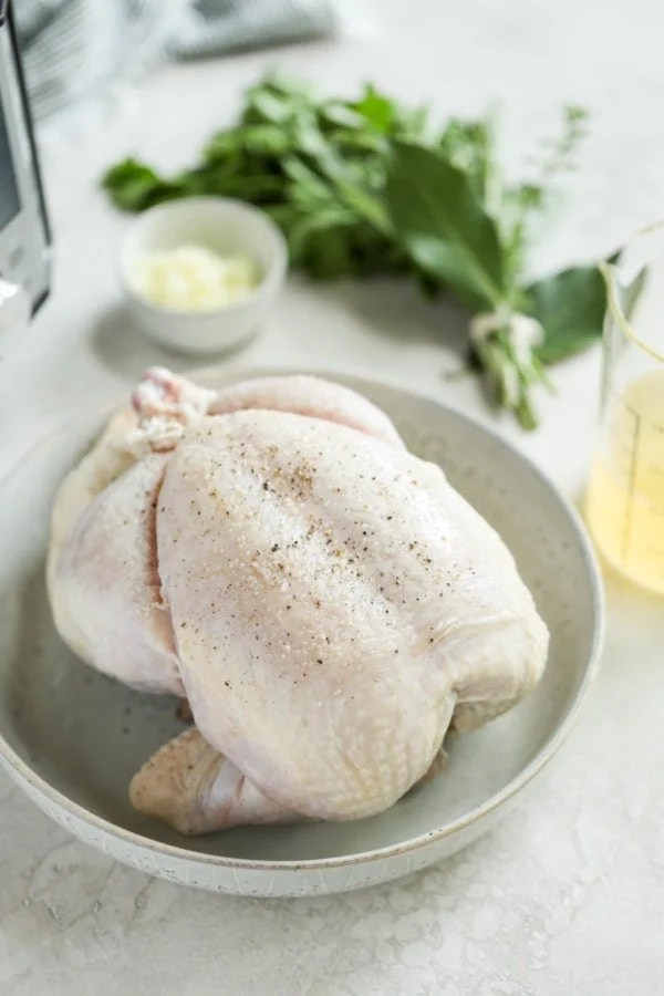 A raw, whole chicken in a bowl with fresh herbs, garlic and broth on the table next to it in preparation to make Instant Pot Whole Chicken.