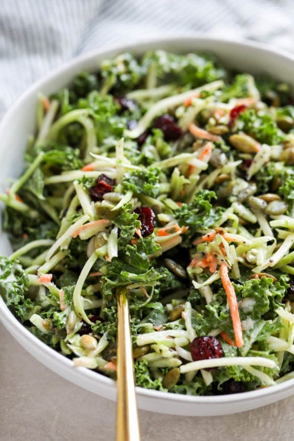 A gold fork filled with creamy broccoli slaw with added kale and dried cranberries ready to be eaten.