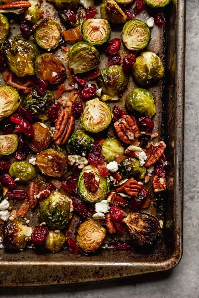 Roasted Brussels Sprouts with Bacon, cranberries, pecans and feta cheese on a pan.