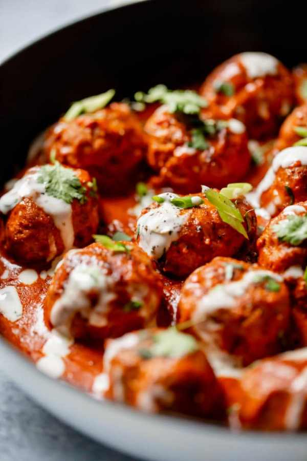 Buffalo Chicken Meatballs in a cast iron skillet drizzled with ranch and topped with green onion and cilantro.