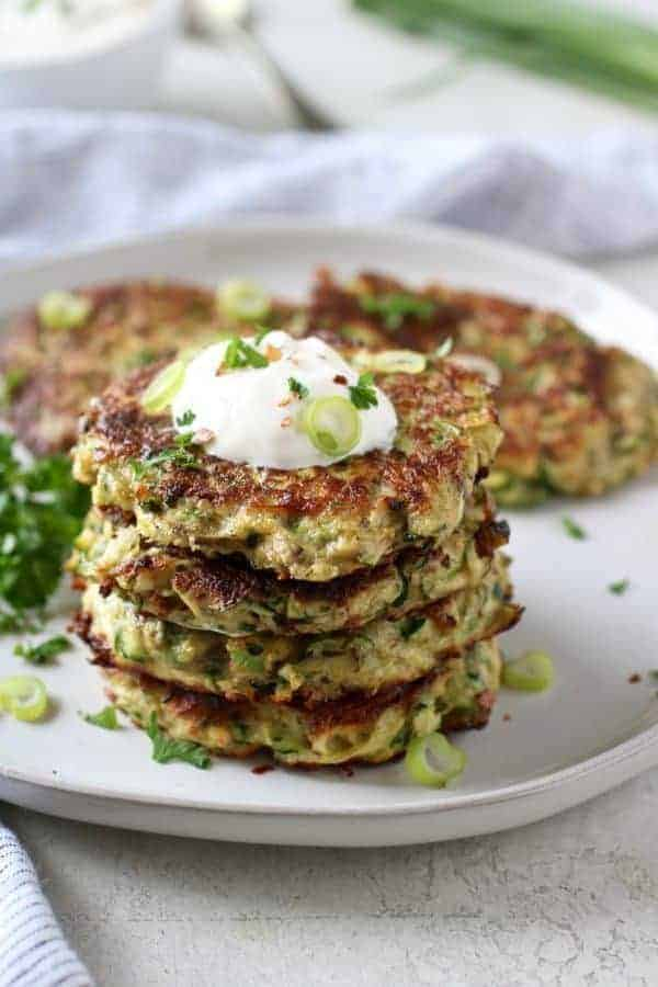 Four zucchini fritters stack on a white plate with a dollop of sour cream on top