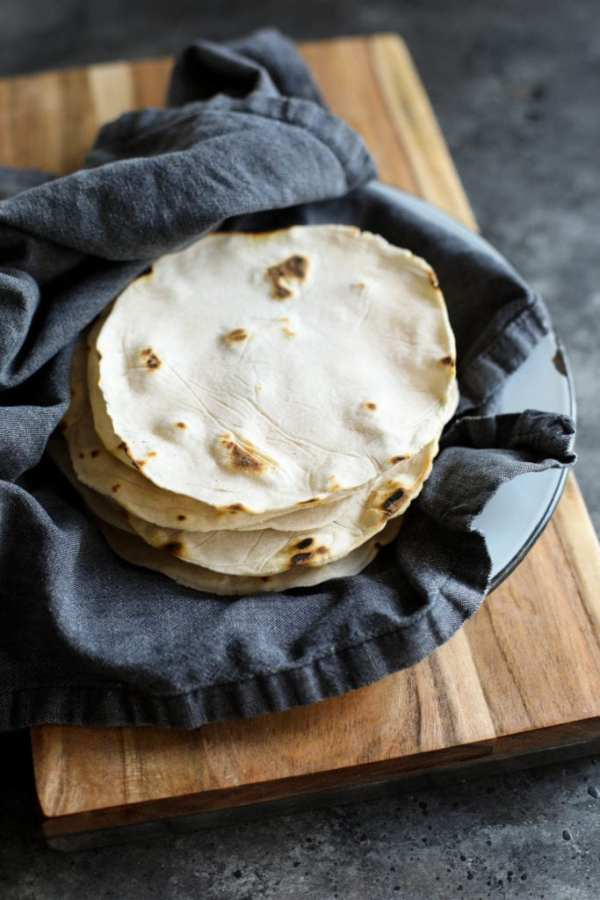 Napkin-lined basket with grain-free tortillas resting on a wooden cutting board