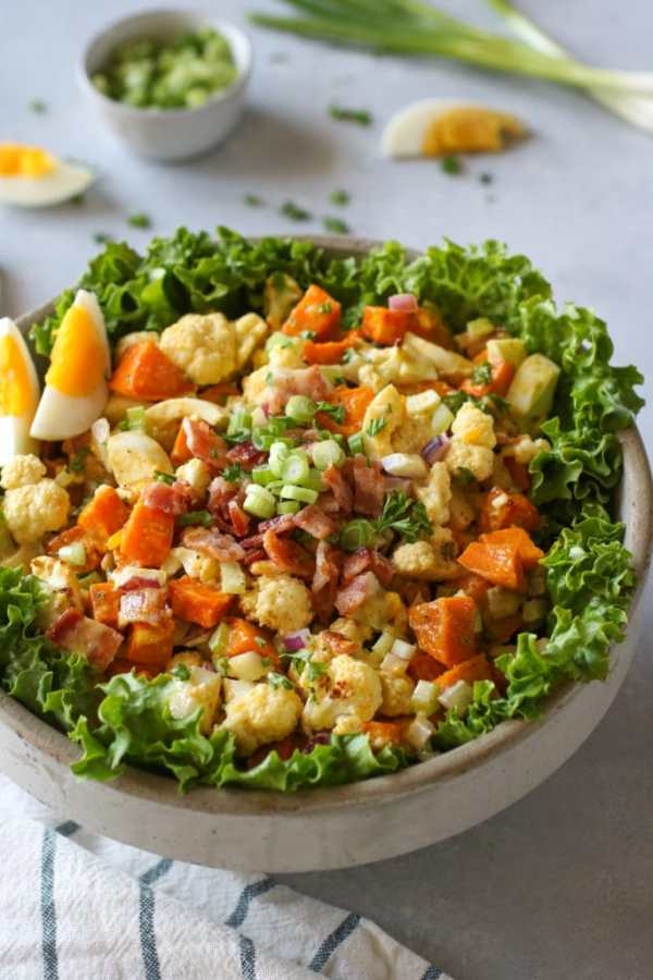 Bowl of lettuce-lined bowl filled with sweet potatoes, cauliflower salad with bacon and hard-boiled egg on side