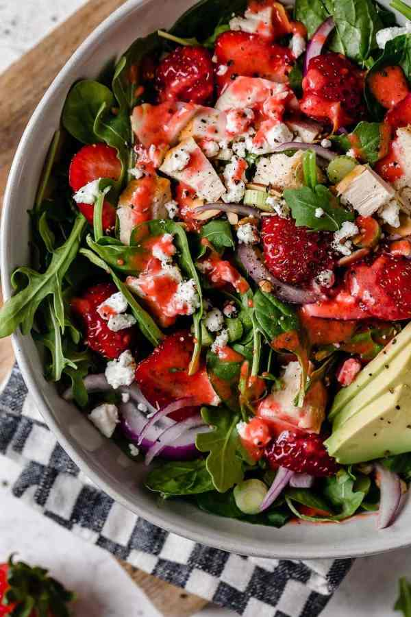Gorgeous closeup overhead shot of Strawberry Spinach Salad with Chicken in a white bowl. Ingredients include greens, sliced strawberries, chunks of chicken, goat cheese crumbles, avocado slices and red onion slices.