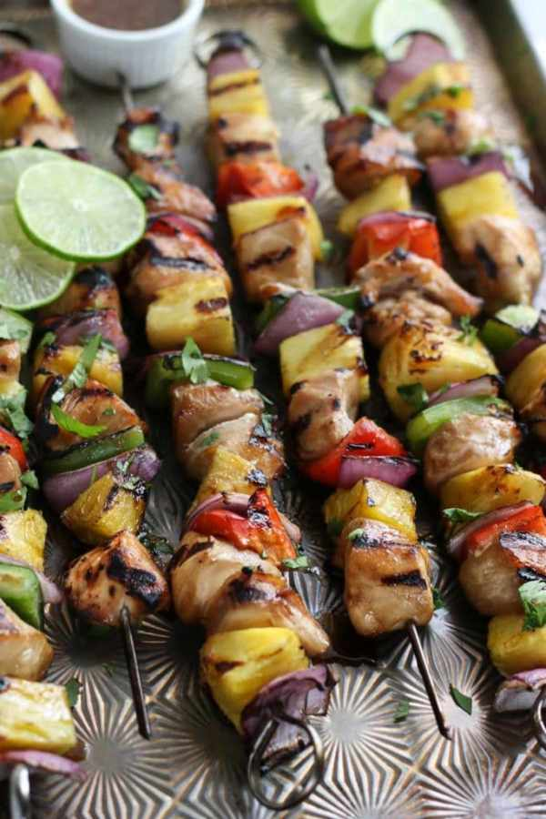 Six chicken kebabs threaded with chicken, pineapple, peppers and onions on a sheet pan with a small dish of dressing toward the back