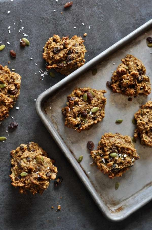 Baked cookies scattered, some on baking sheet and others on dark surface with pumpkin seeds and dried fruit sprinkled around it