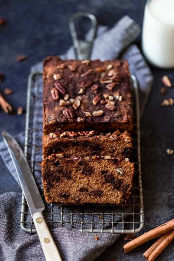 Loaf of chocolate chip pumpkin bread topped with nuts resting on baking rack surrounded by glass of milk, knife and napkin