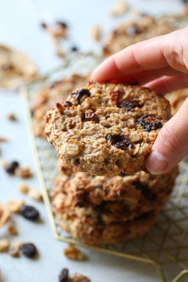 Hand reaching out to grab one oatmeal breakfast cookie off a stack of them on a cooling rack.