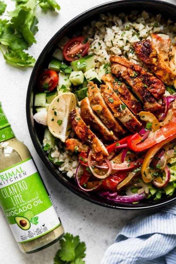 Sheet Pan Chicken Shawarma Bowls: A black bowl filled with cauliflower rice, roasted veggies, sliced chicken thighs, lettuce, cucumbers, and cherry tomatoes and drizzled with a cilantro-lime sauce.