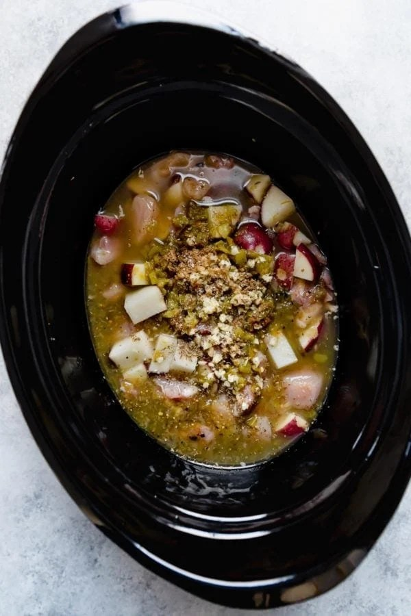 A black slow cooker insert with raw ingredients for Slow Cooker Chicken Chile Verde Stew.