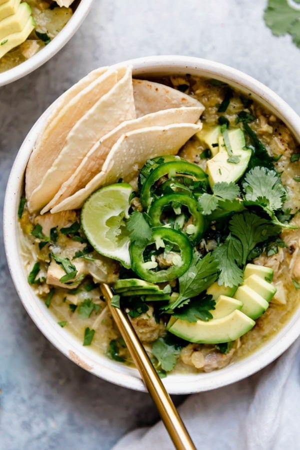 A white bowl filled with Slow Cooker Chicken Chile Verde Stew and topped with fresh cilantro, jalapeño slices, and avocado plus there's a corn tortilla tucked into the side of the bowl for serving.