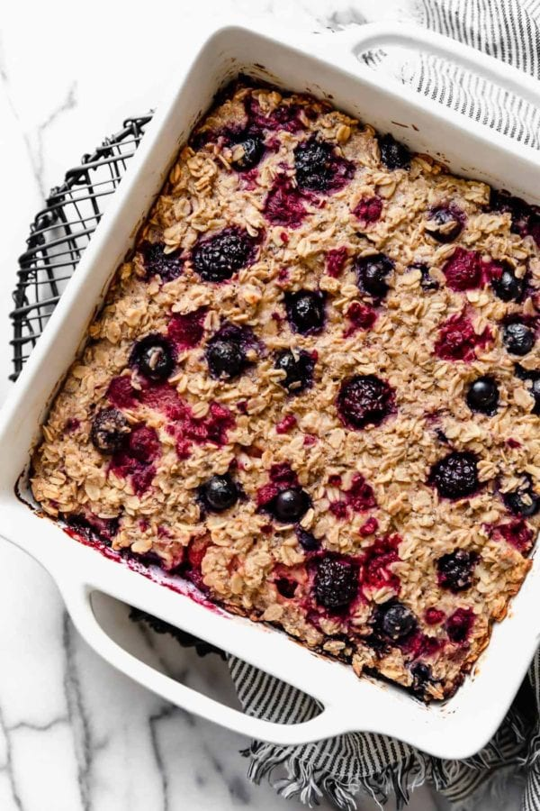 A square white dish filled with Mixed Berry Baked Oatmeal sits atop a wire cooling rack on a marble surface.