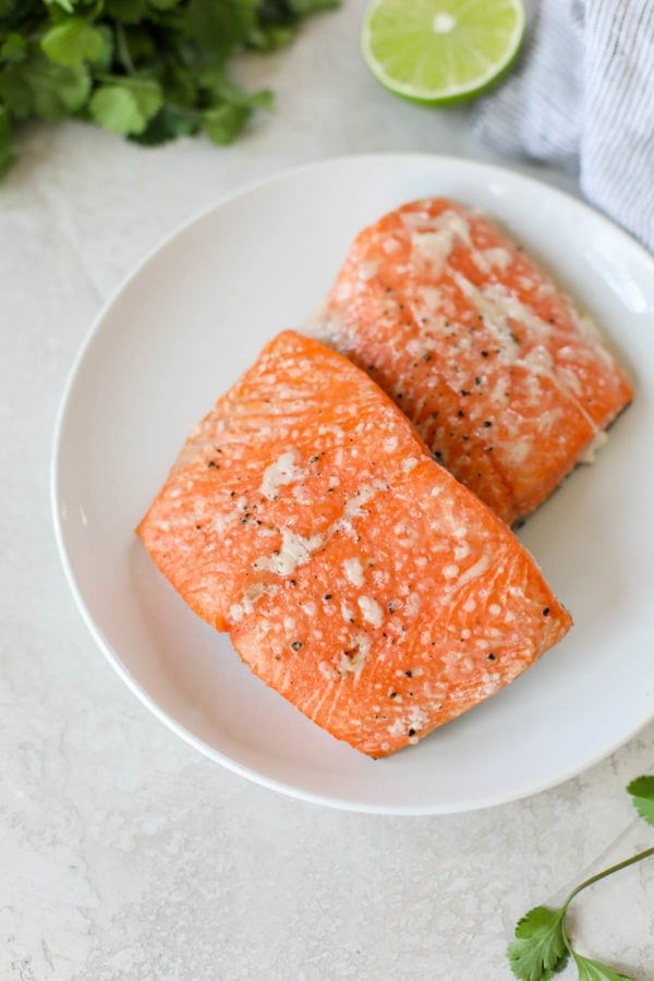 Two perfectly grilled, bright red filets of sockeye salmon on a white plate that have been seasoned with salt and pepper to make Grilled Salmon with Elote Style Veggies.