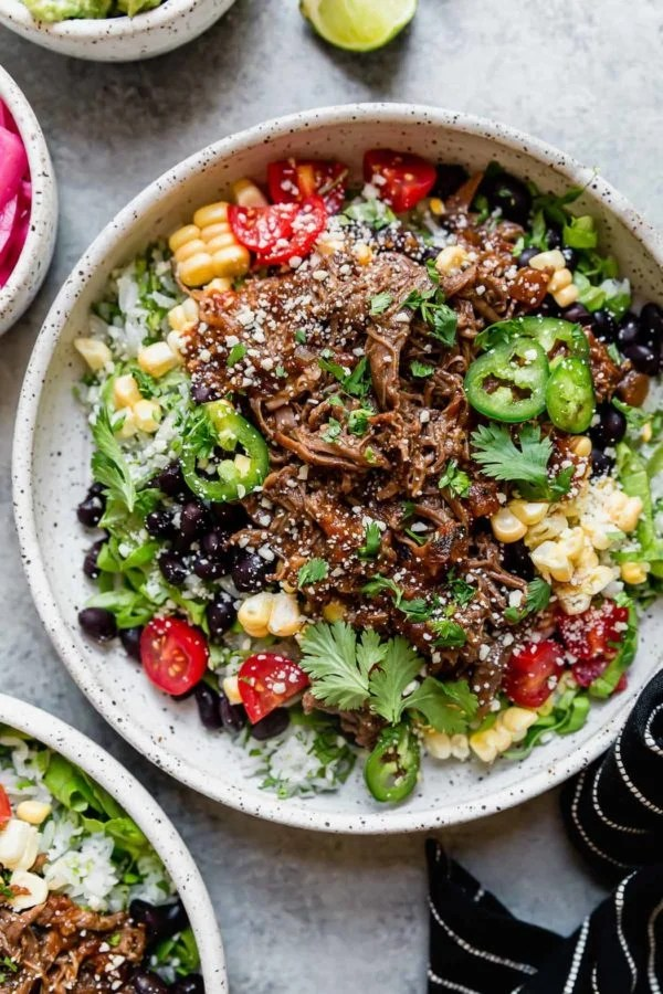 Instant Pot Beef Barbacoa served on a stone plate with all of the toppings - like Chipotle, only better!